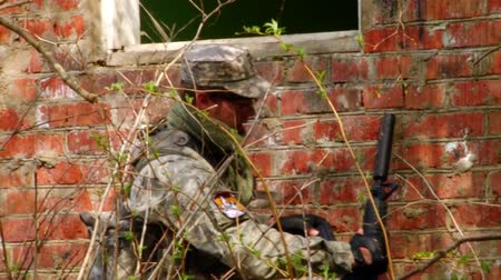 getting : Moscow, Russia - May 09, 2013: Men in military uniforms playing in ruined building of airsoft military polygon. People using a copy of a firearm. Stock Footage
