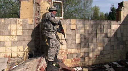 getting ready : Moscow, Russia - May 09, 2013: Man in military uniforms playing in ruined building of military polygon. People using airsoft gun.