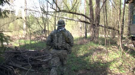 aim : Moscow, Russia - May 09, 2013: Men in military uniforms playing on airsoft military polygon in the forest. People using a copy of a firearm.
