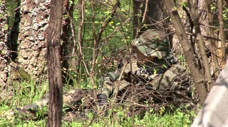 yakın : Moscow, Russia - May 09, 2013: Men in military uniforms playing on airsoft military polygon in the forest. People using a copy of a firearm.