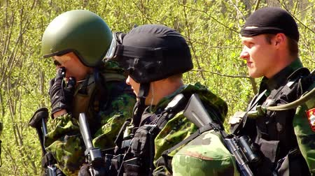 hiding : Moscow, Russia - May 09, 2013: Airsoft game with gun on military polygon. People in military uniforms using a copy of a firearm.