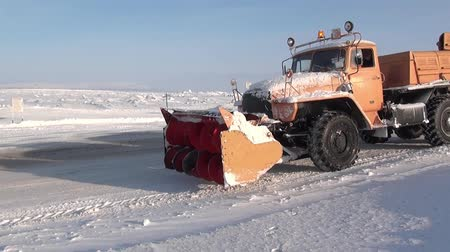neglected : Chukotka, Russia. - 13 April 2013: Snow-removing machine cleans road in Anadyr city on far north. Cold snow town on edge of earth.