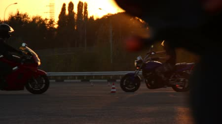rijles : Motorcycle Driving Lessons Moto Gymkhana Motorrijders Bij Zonsondergang Achtergrond Loops Stockvideo