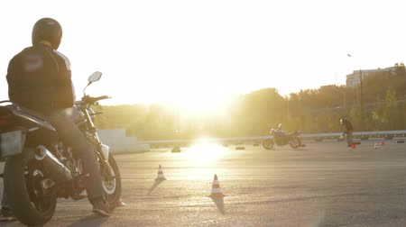 motocykl : motorcyclists standing with a motorcycle at sunset Wideo