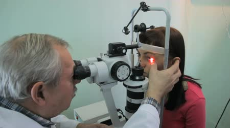 dispensing : Lipetsk, Russian Federation - March 15, 2015: Day of healthy eyes in the clinic 9, the doctor optometrist ophthalmologist Anatoly Petrovich checks vision and the retina of a young woman on a special ophthalmic device open enrollment