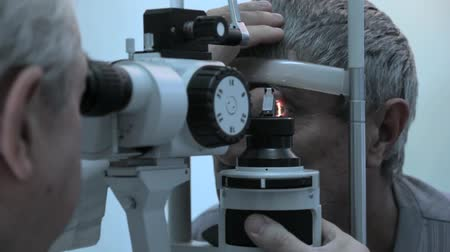 dispensing : Lipetsk, Russian Federation - March 15, 2015: Day of healthy eyes in the clinic 9, the doctor optometrist ophthalmologist Anatoly Petrovich checks vision and the retina of elderly old man on a special ophthalmic device open enrollment Stock Footage
