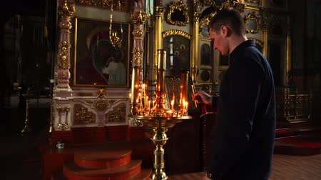 baptized : Elets, Russian Federation - April 2, 2018: A man lights a candle and puts it in the Golden chandelier of the Church. The camera shoots far and then close up. Stock Footage