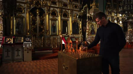 божество : Elets, Russian Federation - April 2, 2018: An Orthodox man lights a candle in the temple. There are many Christian Church icons in the background.
