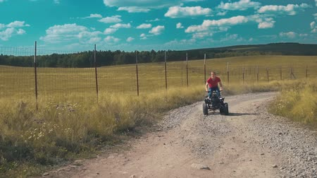 quadbike : Brave young man rides a an ATV on a field.