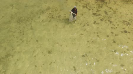 waders : The man goes fishing with a net in the daytime Stock Footage