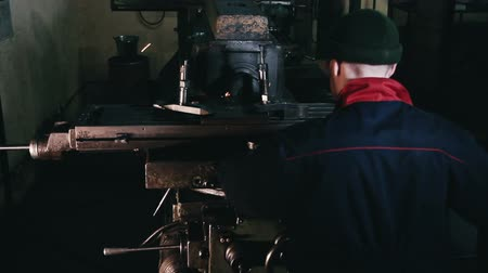 válvula : Man in hat is working at a machine at a factory