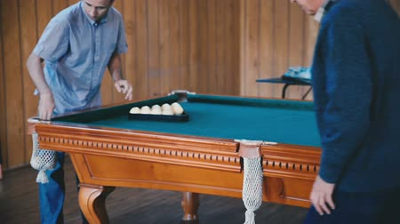 sinuca : Man is making together balls for playing billiards in the room