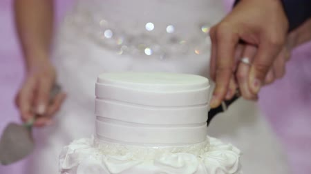 wedding cake : A groom and fiancee cut a wedding cake and lay it on a dish. CU. Stock Footage