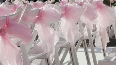 zęby : Rows of white chairs with pink ribbons. Wideo