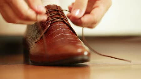 sapato : Man tying shoelaces on expensive brown shoes