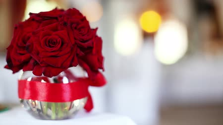 imagem : It focus and pan with a bouquet of red roses in a vase Vídeos