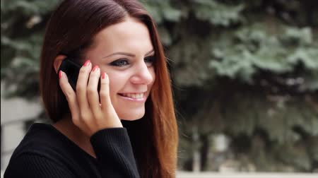 telefones : Beautiful girl looks up and starts talking on mobile phone, smiling while doing so.