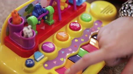 toy : Mom and child playing on a plastic toy piano