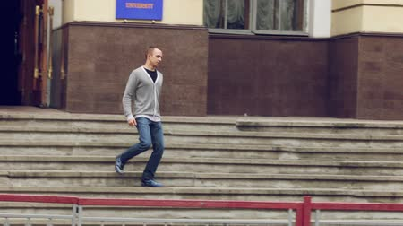 trabalhar fora : Student coming out of the university and walks down the stairs Vídeos