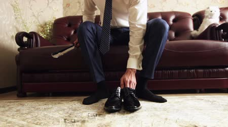 cipőfűző : Man comes and puts expensive black shoes.