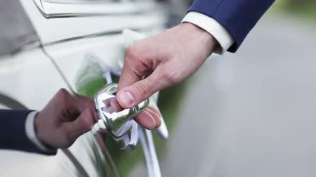 Дверная ручка : Man in a expensive suit opens the door decorated cars and closes it