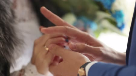 halkalar : Groom wears a wedding ring for bride and wraps her arms with his hands