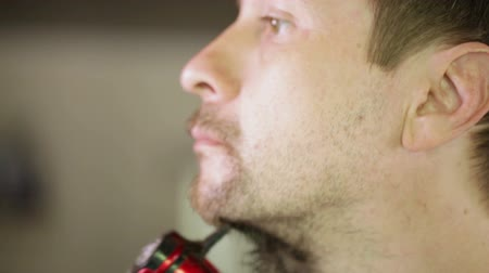 barbear : Young man shaves beard electric shaver