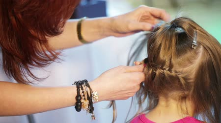 cabeça e ombros : Hairdresser braids a young girl hair