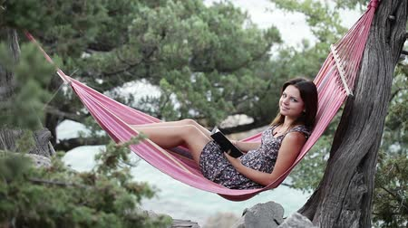 гамак : Lying in hammock girl speaks on smartphone