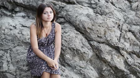 urge : Girl sitting on a rock requests do for her service Stock Footage