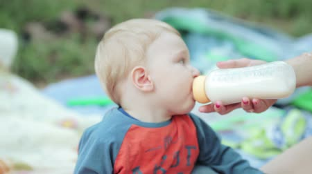 бутылки : Nature baby boy in mothers arms with bottle in his mouth