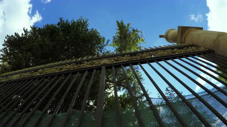 gates : Camera shoots from below wrought iron fence