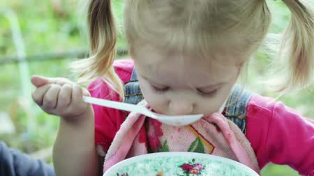 zupa : Girl on nature of spoon eating soup Wideo