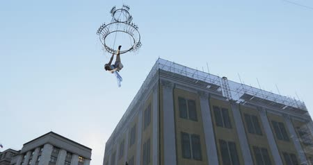csillár : Girl acrobat in white dress in the air above the street in a big chandelier on the rope Stock mozgókép
