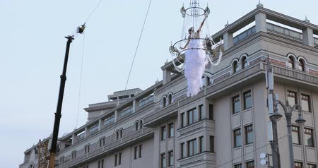 tverskaya : Girl acrobat in white dress in the air above the street in a big chandelier on the rope Stock Footage