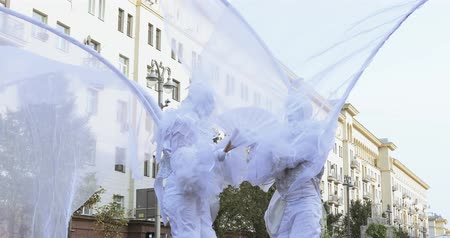 akrobatikus : Dancers on stilts in suits of white elves or butterflies with inflatable balls
