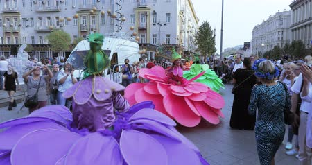 Dancers on stilts in suits of colorful large flowers