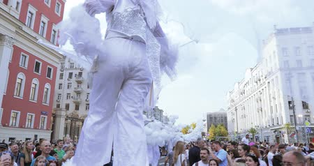 Dancers on stilts in suits of white elves or butterflies with inflatable balls