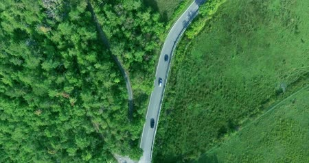 точка зрения : Aerial camera shot along the busy road, near the field and the f