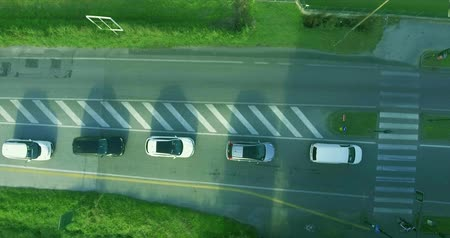 управлять : Cars on the road stopped for a red light, skipping the bicyclist. A cyclist crosses the roadway through a pedestrian crossing aerial shot