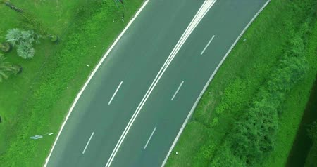 управлять : Car moving on the road, passing near a double solid white marking line. Aerial shot