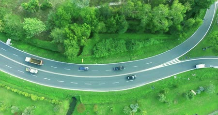 управлять : Movement of cars and trucks along the highway in the forest, aerial shot, top view
