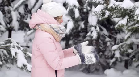 mittens : Young woman shakes off her mittens from the snow, standing in the winter forest, in the background of fluffy snowy fir trees slow motion