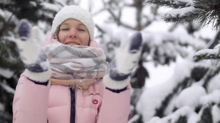 mittens : Active young woman in a winter forest clapping, shaking mittens from snow slow motion