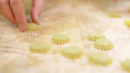 uložit : Close-up chefs hands moving the semi-finished ravioli on a table strew with flour, slow motion