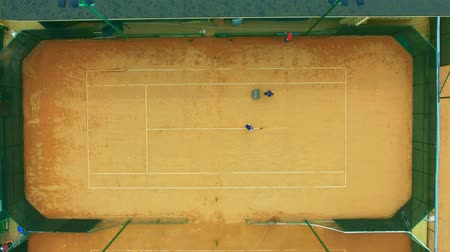 metin alanı : People prepare a tennis court for the match. Marking, leveling the court surface, cleaning. View from above, aerial shot