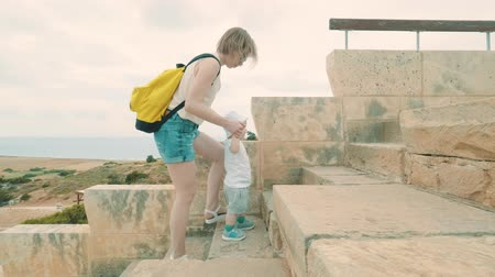 gladiatorial : Mother keeps her son, helps child to climb the steps of the amphitheater in Kourion Cyprus Theatre. Slow motion.