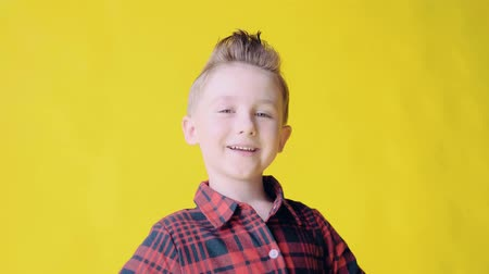 sortudo : Portrait of happy smiling European blonde young boy with a modern fashion haircut, slow motion