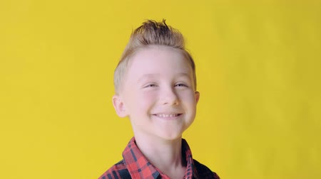 sortudo : SLOW MO: Cheerful nice young smiling boy looking at the camera. Blonde boy on a yellow background