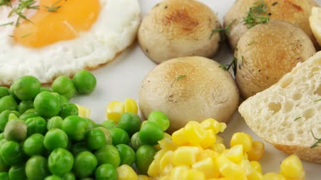 scrambled eggs : Full breakfast with scrambled eggs, sausages and vegetables in big white plate (loop)